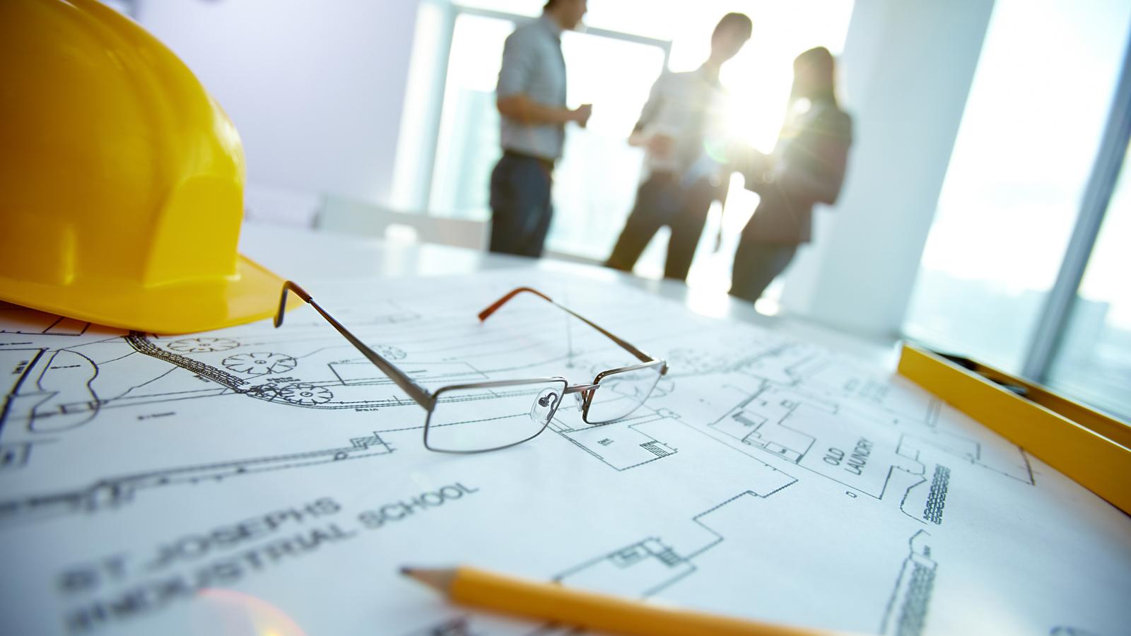 Employees discuss blueprints