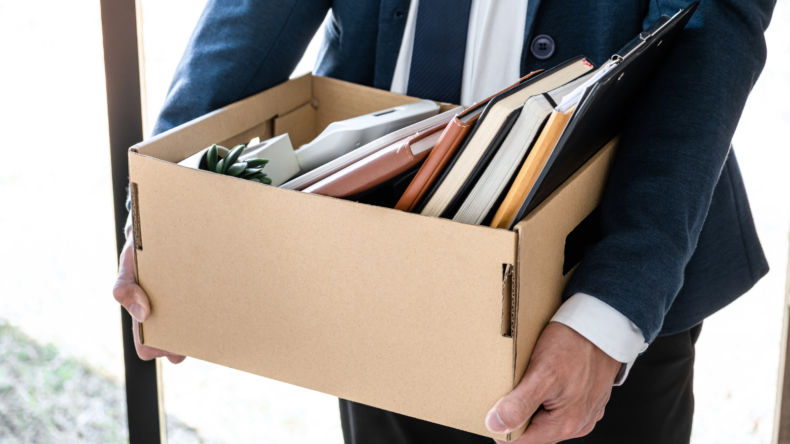 Person carrying a cardboard box containing personal office items